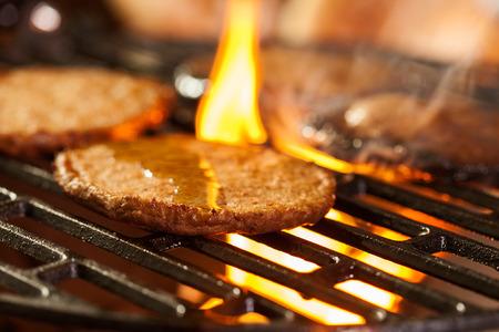 under fire: Las hamburguesas en una parrilla con fuego bajo. Enfoque selectivo