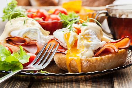 comida inglesa: Huevos Benedict en panecillos tostados con jamón y salsa