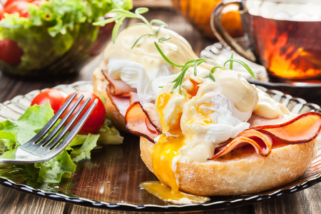 Eggs Benedict on toasted muffins with ham and sauce Stockfoto