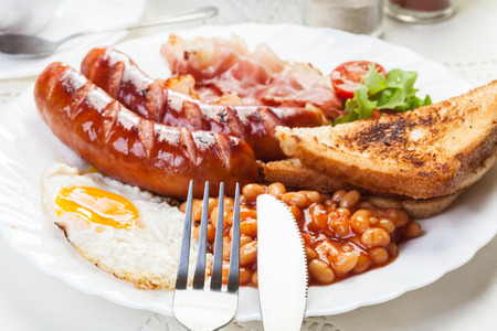 english food: Full English breakfast with bacon, sausage, fried egg, baked beans and tea Stock Photo
