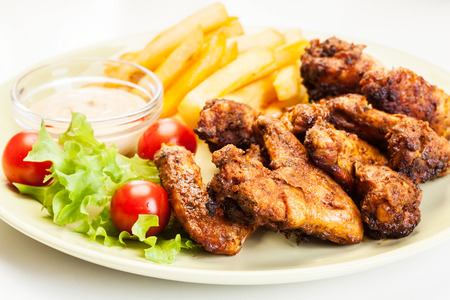 Chicken wings with fries french and spicy sauce on a plate Stock Photo