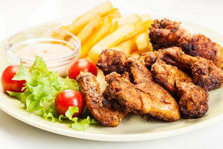Hähnchenflügel mit Pommes frites Französisch und pikanter Sauce auf einem Teller Standard-Bild - 31330614