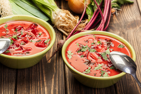 Beetroot soup with fresh vegetables in a bowl on a wooden table Stock Photo