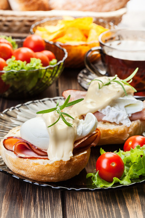 Eggs Benedict on toasted muffins with ham and sauce Standard-Bild