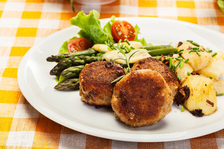 Meatballs served with boiled potatoes and asparagus on a plate