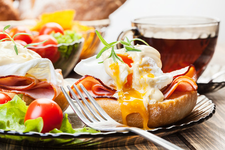 breakfast eggs: Eggs Benedict on toasted muffins with ham and sauce Stock Photo