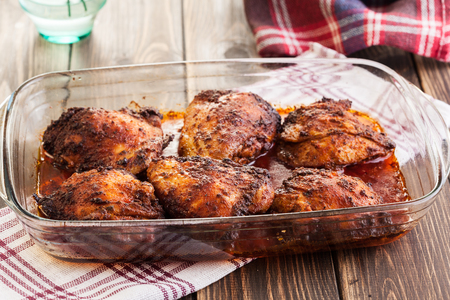 Roasted chicken drumsticks in casserole dish. Selective focus Stock Photo
