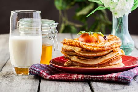 Amerikaanse pannenkoeken met honing, fruit en een glas melk