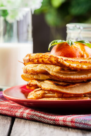 American pancakes with honey, fruit and glass of milk photo