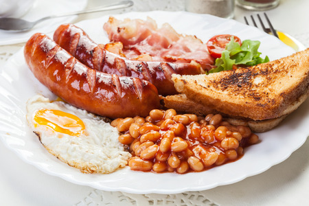 british foods: Full English breakfast with bacon, sausage, fried egg, baked beans and tea Stock Photo