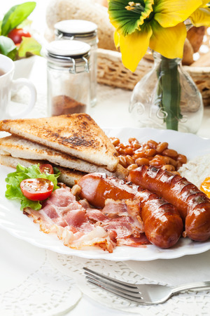 Full English breakfast with bacon, sausage, fried egg, baked beans and tea photo