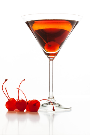 Manhattan cocktail garnished with a cherry on white background photo