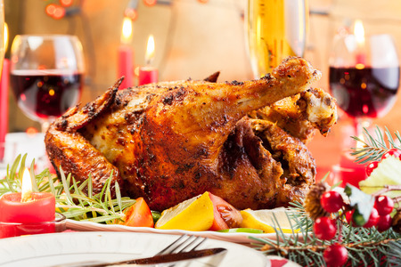 Baked chicken for Christmas dinner on festive table Standard-Bild