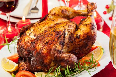 Baked chicken for Christmas dinner on festive table Stock Photo