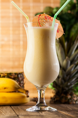 Pina Colada over wooden background garnished pineapple photo