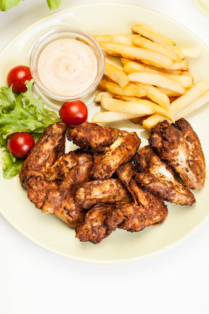 Chicken wings with fries french and spicy sauce on a plate photo