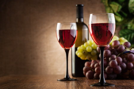 Glasses of red wine and bottle on wooden table photo
