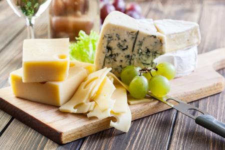 Verschillende soorten kaas op een houten bord Stockfoto
