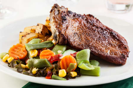 grilled potato: Fried pork with roasted potatoes and vegetables salad Stock Photo