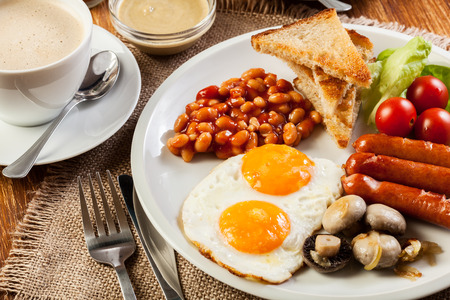 british foods: English breakfast with sausage, eggs and beans
