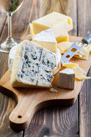 cheeses: Assorted cheeses on wooden board