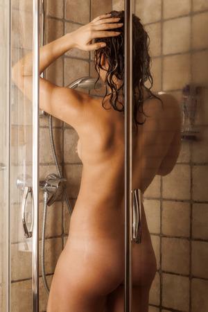 personas tomando agua: Mujer joven hermosa que toma la ducha en el baño