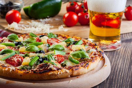 pizza: Hawaii pizza con cerveza servida en la tabla de cortar