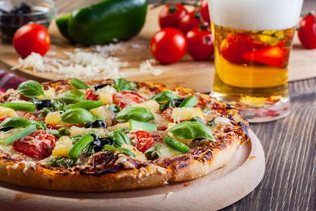 Pizza Hawaï met bier geserveerd op snijplank