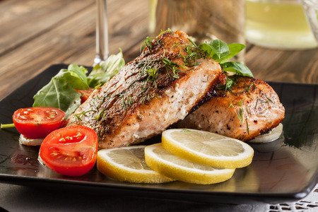 Fried salmon steak with vegetables and lemon