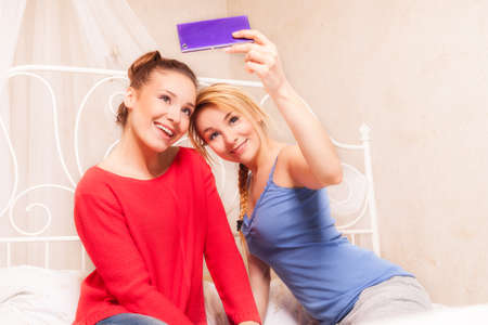 Two girls doing themselves photo in a bedroom photo