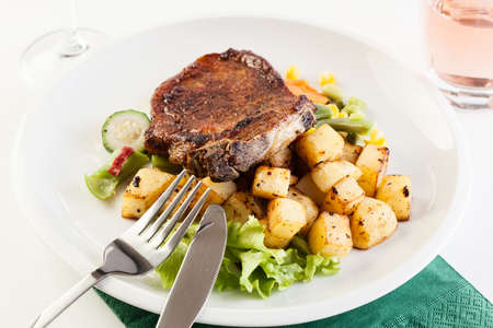 Fried pork with roasted potatoes and vegetables salad Stock Photo
