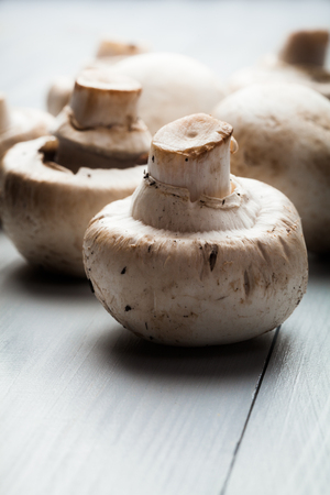 button mushrooms: White button mushrooms on a wooden blue table. Dark lighting