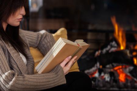 Jonge vrouw leest een boek door open haard