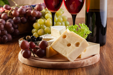 wine colour: Cheese with a bottle and glasses of red wine on wooden table