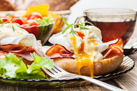 benedict: Eggs Benedict on toasted muffins with ham and sauce Stock Photo
