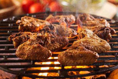 Grilling chicken wings on barbecue grill. Selective focus