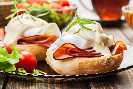 egg cup: Eggs Benedict on toasted muffins with ham and sauce Stock Photo