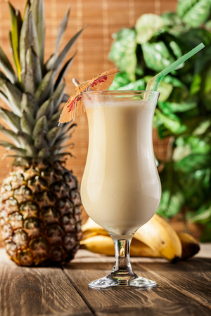 colada: Pina Colada over wooden background garnished pineapple