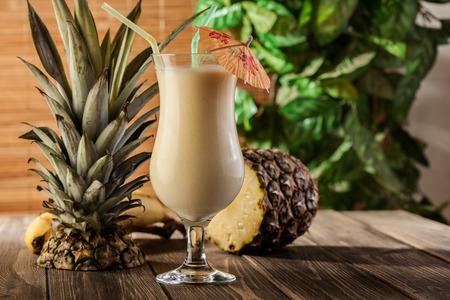 Pina Colada over houten gegarneerd ananas Stockfoto