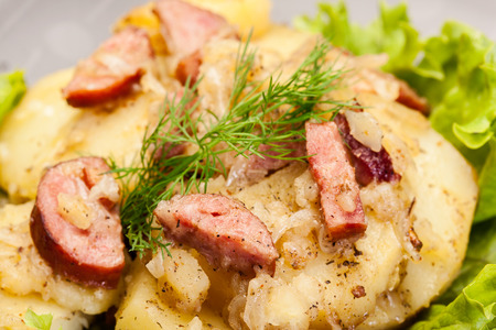 scalloped: Scalloped potatoes with sausage and bacon on a plate