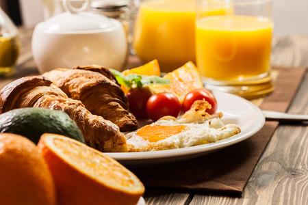 Ontbijt met croissant sinaasappelsap eieren einde