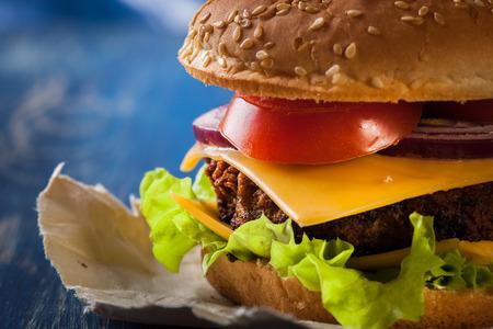 alimentos y bebidas: Primer de la hamburguesa en el papel y la mesa azul