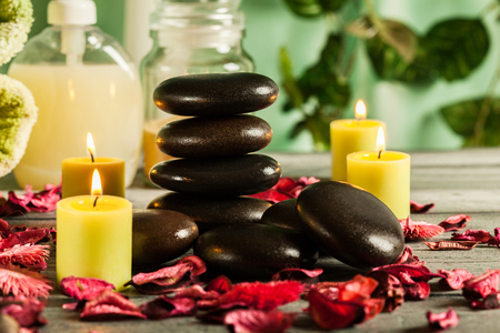 Spa still life with hot stones essential oil and candles Stock Photo