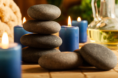 hot stones: Spa still life with hot stones essential oil and candles Stock Photo