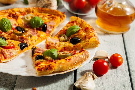 smack: Pizza with bacon olives and jalapeno pepper on a plate Stock Photo