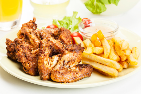 Chicken wings with fries french and spicy sauce on a plate Фото со стока