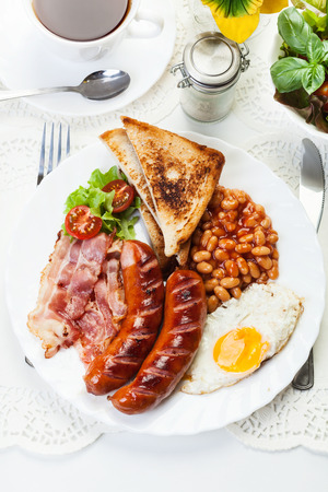bacon baked beans: Full Angielski breakfast with fried egg bacon sausage baked beans and tea