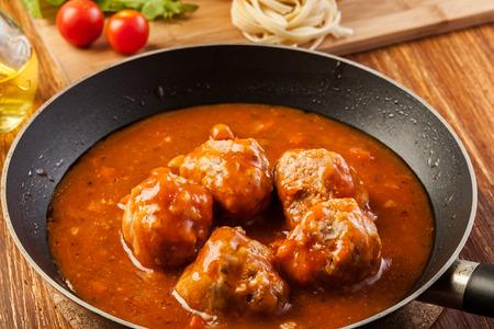 Meatballs with tomato sauce on pan photo