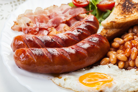bacon baked beans: Full English breakfast with bacon, sausage, fried egg, baked beans and tea Stock Photo