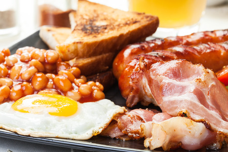 'english: Full English breakfast with bacon, sausage, fried egg, baked beans and orange juice